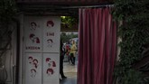 In this Thursday June 4 , 2020 photo moviegoers stand outside the entrance of the Thision outdoor summer cinema where moviegoers watch films under the ancient Acropolis. Cine Thision is one of the oldest open-air movie theaters in Athens, built in 1935. (AP Photo/Petros Giannakouris)