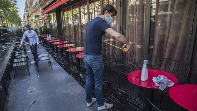 Pierre-Antoine Boureau handles a tape measure as he prepares the terrace of a restaurant in order to respect social distancing to help curb the spread of the coronavirus in Paris, Monday, June 1, 2020. (AP Photo/Michel Euler)