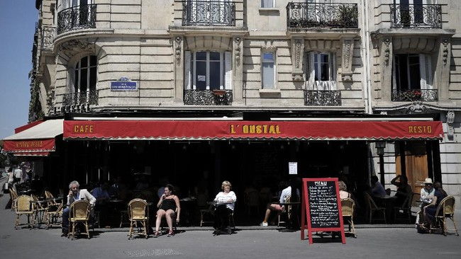 People sit on the terrace of a cafe in Paris, Tuesday, June 2, 2020. Parisians who have been cooped up for months with take-out food and coffee will be able to savor their steaks tartare in the fresh air and cobbled streets of the City of Light once more, albeit in smaller numbers. (AP Photo/Christophe Ena)