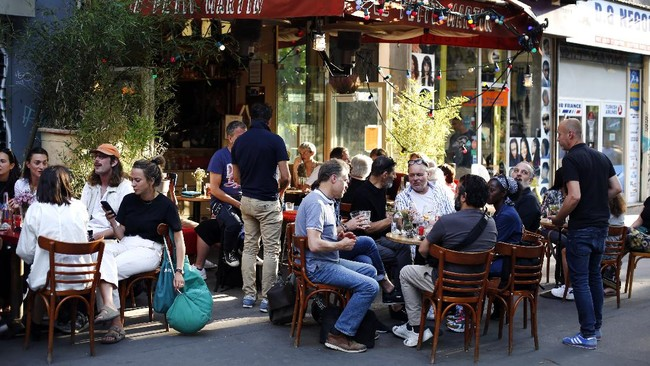 People sit on the terrace of a cafe in Paris, Tuesday, June 2, 2020. Paris City Hall authorized the reopening of outside seating areas but indoor tables remain closed to customers until at least June 22. (AP Photo/Thibault Camus)