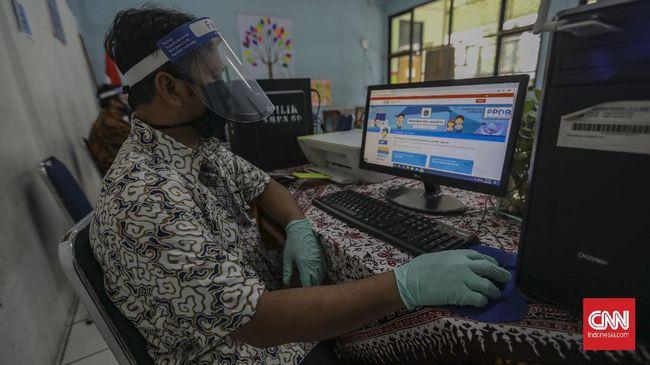 Petugas mempersiapkan fasilitas yang akan digunakan untuk penerimaan peserta didik baru (PPDB) di SMP Negeri 60 Jakarta, Kamis, 11 Juni 2020. Kementerian Pendidikan dan Kebudayaan (Kemendikbud) secara resmi menetapkan tahun ajaran baru 2020-2021 dimulai pada 13 Juli 2020. CNN Indonesia/Bisma Septalisma