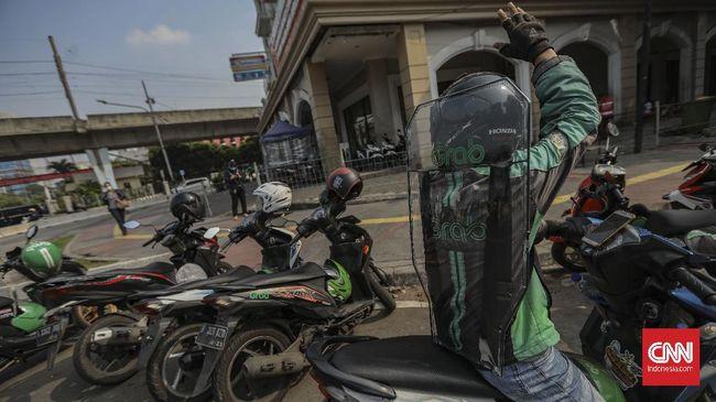 Pengemudi ojek daring mengenakan sekat pelindung saat melintas di kawasan jalan Kendal, Jakarta, Kamis, 11 Juni 2020. Penggunaan sekat pelindung untuk pembatasan antara pengemudi dan penumpang tersebut sebagai bentuk penerapan protokol kesehatan guna meminimalisir risiko penyebaran virus COVID-19 dalam menghadapi era normal baru. CNN Indonesia/Bisma Septalisma