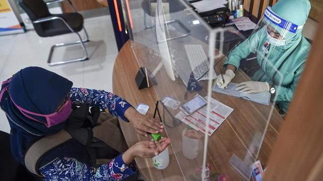 Petugas dengan menggunakan pelindung wajah (face shield) melayani calon penumpang di Stasiun pasar Senen, Jakarta, Jumat (12/6/2020). PT KAI Daop 1 Jakarta melakukan adaptasi persiapan pelaksanaan prosedur tetap masa adaptasi kebiasaan baru antara lain dengan penggunaan masker, pelindung wajah, pemeriksaan suhu tubuh dan jaga jarak di tengah masa pandemi guna pencegahan penyebaran COVID-19. ANTARA FOTO/Nova Wahyudi/pras.