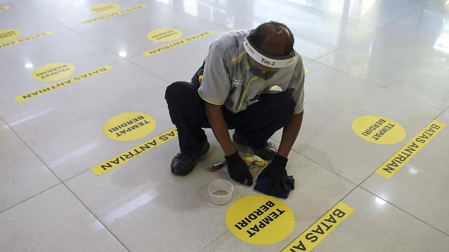 Petugas dengan menggunakan pelindung wajah (face shield) memasang tanda untuk menjaga jarak di stasiun Pasar Senen, Jakarta, Jumat (12/6/2020). PT KAI Daop 1 Jakarta melakukan adaptasi persiapan pelaksanaan prosedur tetap masa adaptasi kebiasaan baru antara lain dengan penggunaan masker, pelindung wajah, pemeriksaan suhu tubuh dan jaga jarak di tengah masa pandemi guna pencegahan penyebaran COVID-19. ANTARA FOTO/Nova Wahyudi/pras.