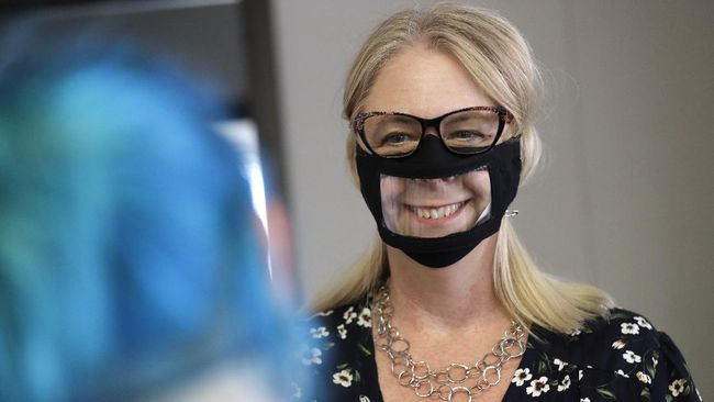 In this June 3, 2020, photo, Chris LaZich, of Fleet Science Center, wears a mask with a window as she talks with Delpha Hanson in San Diego. Face coverings to curb the spread of the coronavirus are making it hard for people who read lips to communicate. That has spurred a slew of startups making masks with plastic windows to show one's mouth. The companies are getting inundated with orders from family and friends of deaf people, people helping English learners see the pronunciation of words, and even hospitals that want their patients to be able to see smiles. (AP Photo/Gregory Bull)