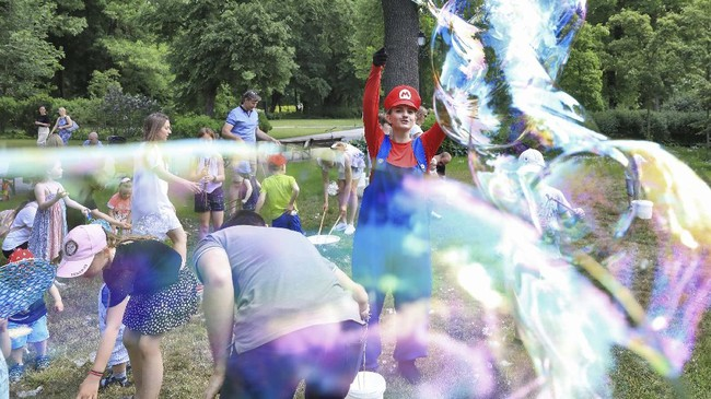 An entertainer dressed up as Super Mario the Italian plumber makes giant bubbles  for children in the Bernardine Garden during a tourism event to mimicking the Italian holiday experience in Vilnius, Lithuania on June 6, 2020. - With virus travel restrictions preventing summer holidays abroad, Lithuania's capital is offering a low-cost alternative by mimicking the look and feel of different countries at weekends. (Photo by PETRAS MALUKAS / AFP)