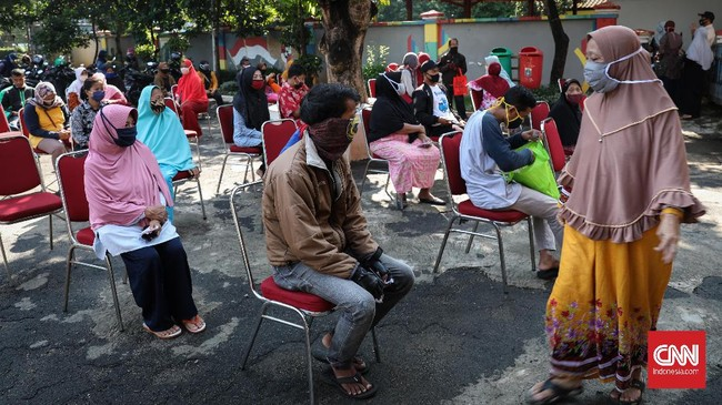 Warga antre dan berjarak untuk mengambil paket bansos di Kelurahan Pondok Kelapa, Jakarta, Jumat, 12 Juni 2020. Bansos program keluarga harapan (PKH) sudah berlangsung sejak April untuk melindungi keluarga prasejahtera dari dampak Covid-19. Isi bansos yang diterima warga berupa beras, telur, jeruk dan ayam potong. CNNIndonesia/Safir Makki