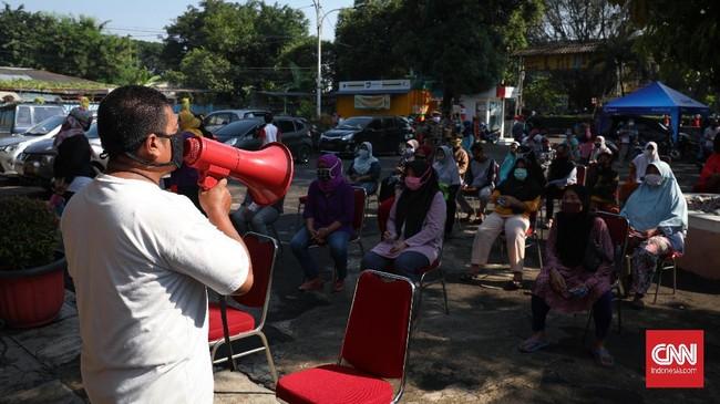 Petugas mengingatkan warga untuk jaga jarak saat antre mengambil paket bansos di Kelurahan Pondok Kelapa, Jakarta, Jumat, 12 Juni 2020. Bansos program keluarga harapan (PKH) sudah berlangsung sejak April untuk melindungi keluarga prasejahtera dari dampak Covid-19. Isi bansos yang diterima warga berupa beras, telur, jeruk dan ayam potong. CNNIndonesia/Safir Makki