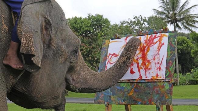 Zella menggoreskan kuas di atas kertas di taman Lumbini, Borobudur.