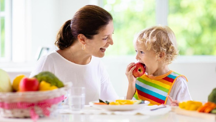 Mother feeding child vegetables. Mom feeds kid in white kitchen with window. Baby boy sitting in high chair eating healthy lunch of steamed carrot and broccoli. Nutrition, vegetarian diet for toddler