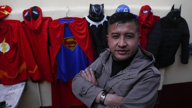 Art teacher Jorge Manolo Villarroel poses for a photo next to his superhero costumes, after imparting one of his online classes from his home, amid the new coronavirus pandemic in La Paz, Bolivia, Tuesday, June 10, 2020. Villarroel makes the costumes he wears.