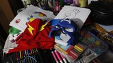 The superhero masks of The Flash and Captain America sit on top on of art supplies that teacher Jorge Manolo Villarroel uses to impart online classes from his home, amid the new coronavirus pandemic in La Paz, Bolivia, Tuesday, June 9, 2020. Villarroel's modest room is filled with the masks and costumes of his characters, along with images of Christ, several Roman Catholic saints, revolutionary icon Che Guevara, and his parents. (AP Photo/Juan Karita)