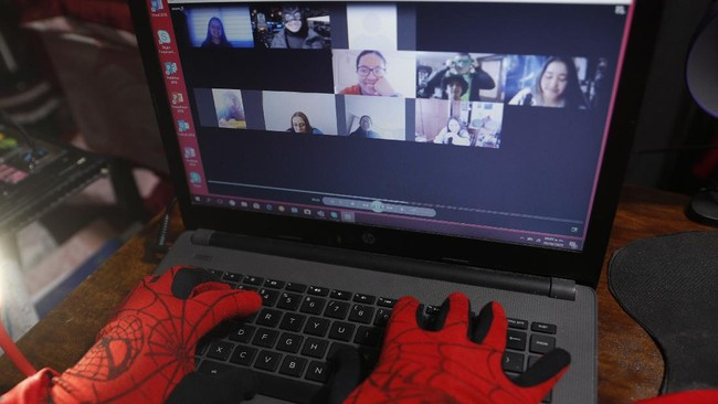 Art teacher Jorge Manolo Villarroel, wearing a Spider-Man costume, teaches an online class from his home, amid the new coronavirus pandemic in La Paz, Bolivia, Tuesday, June 9, 2020. His classes have become so popular that siblings fight for the laptop to learn from this costumed teacher. (AP Photo/Juan Karita)