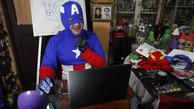 Art teacher Jorge Manolo Villarroel, wearing a Captain America costume, teaches an online class from his home, amid the new coronavirus pandemic in La Paz, Bolivia, Tuesday, June 9, 2020. His classes have become so popular that siblings fight for computer time to learn from this costumed teacher. (AP Photo/Juan Karita)