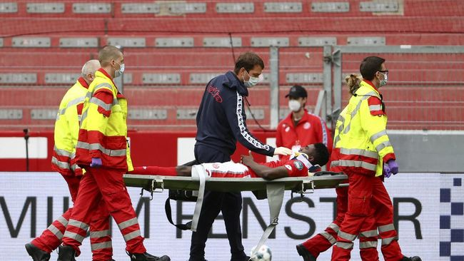 Mainz's Taiwo Awoniyi is stretchered off after sustaining an injury during the German Bundesliga soccer match between 1. FSV Mainz 05 and FC Augsburg in Mainz, Germany, Sunday, June 14, 2020. Because of the coronavirus outbreak all soccer matches of the German Bundesliga take place without spectators. (Kai Pfaffenbach/Pool via AP)