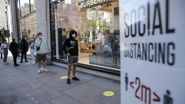 People wait in line for the opening of the Selfridges department store in London, Monday, June 15, 2020. After three months of being closed under coronavirus restrictions, shops selling fashion, toys and other non-essential goods are being allowed to reopen across England for the first time since the country went into lockdown in March.(AP Photo/Matt Dunham)