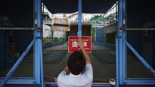 An employee posts a sign to suspend indoor facilities at the newly-opened Yomiuriland amusement park in Tokyo, Tuesday, June 16, 2020. The park has been closed since the end of March as a part of the precautions to help curb the spread of the  coronavirus. (AP Photo/Eugene Hoshiko)