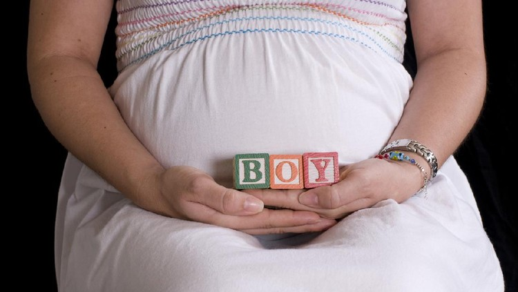 Pregnant woman with alphabet cubes spelling Boy