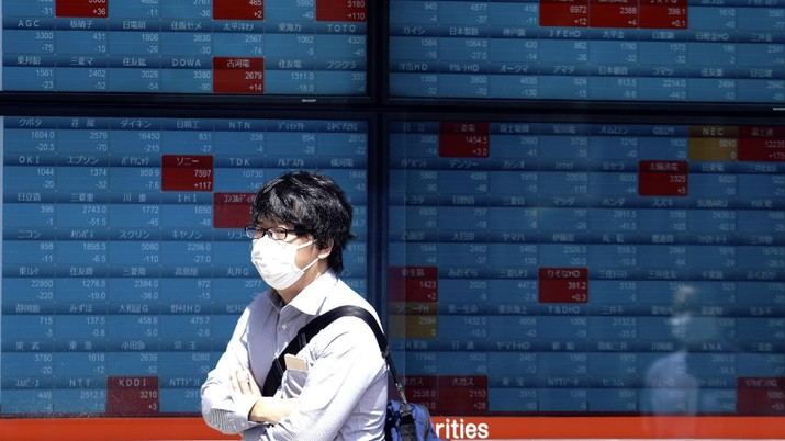 A man walks in front of an electronic stock board showing Japan's Nikkei 225 index at a securities firm in Tokyo Wednesday, June 17, 2020. Major Asian stock markets declined Wednesday after Wall Street gained on hopes for a global economic recovery and Japan's exports sank. (AP Photo/Eugene Hoshiko) - PT Rifan Financindo