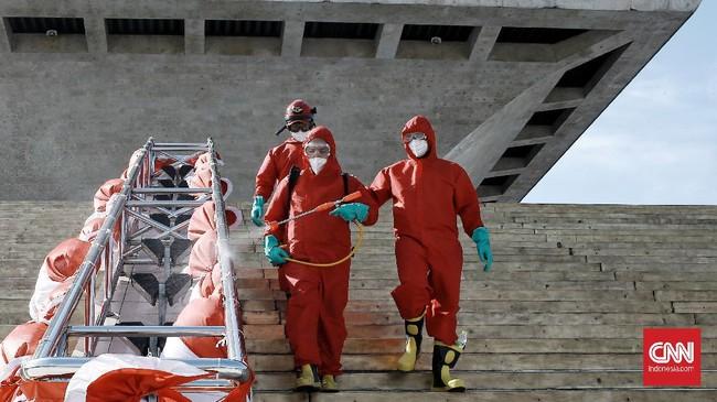 Petugas pemadam kebakaran menyemprotkan cairan disinfektan di kompleks Monumen Nasional (Monas), Jakarta, Rabu (17/6/2020). CNN Indonesia/Andry Novelino
