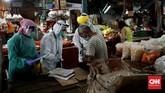 Petugas medis Puskesmas Kecamatan Gambir mengambil sampel lendir warga saat tes Swab di Pasar Thomas,  Jakarta, Rabu, 17 Juni 2020. Tes swab untuk memutus mata rantai penyebaran Covid-19 itu diperuntukan bagi para pedagang pasar. CNN Indonesia/Safir Makki