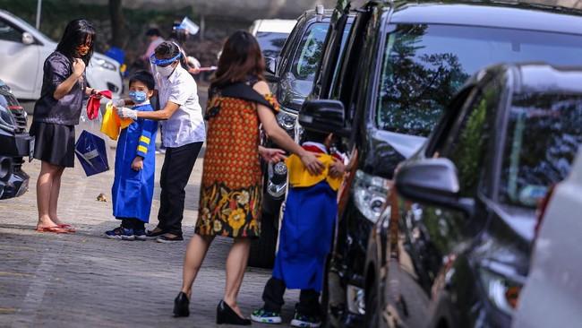 Siswa sekolah Stella Maris bersiap sebelum mengikuti acara kelulusan secara 'drive thru' di Stella Maris School, Kelapa Dua, Kabupaten Tangerang, Banten, Selasa (9/6/2020). Kegiatan wisuda tersebut digelar secara 'drive thru' guna menghindari kerumunan yang bisa menjadi medium penyebaran COVID-19. ANTARA FOTO/Fauzan/foc.