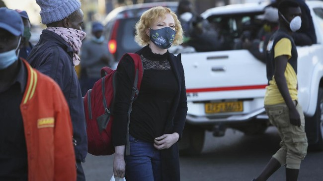 Brenda Mudzimu, founder of Miss Albinism Trust, walks on the streets of Harare, in this Monday, June, 8, 2020 photo. Mudzimu says her trust focuses on success and not pity and that they also offer career guidance workshops and support sessions for people with albinism. However the economic downturn caused by restrictions to combat the spread of COVID-19 means that many people with albinism are struggling to put food on the table, let alone afford essential items such as sun block, skin lotions and other medications. (AP Photo/Tsvangirayi Mukwazhi)