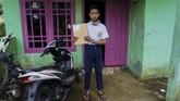 Pelajar SMP N 4 Bawang, Khoerul Risal, menunjukkan amplop berkas lembar tugas yang diantarkan langsung oleh gurunya di Pranten, Kecamatan Bawang, Kabupaten Batang, Jawa Tengah.