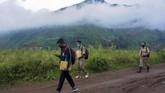 Kepala Sekolah SMP N 4 Bawang Mulud Sugito (kanan) dan guru Wiyata Bhakti berjalan kaki guna mengantar lembar tugas siswa langsung ke  rumahnya di Pranten, Kecamatan Bawang, Kabupaten Batang, Jawa Tengah.
