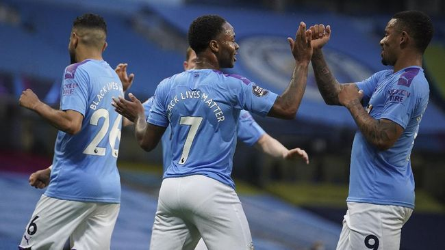 Manchester City's Raheem Sterling, center, celebrates after scoring the opening goal during the English Premier League soccer match between Manchester City and Arsenal at the Etihad Stadium in Manchester, England, Wednesday, June 17, 2020. The English Premier League resumes Wednesday after its three-month suspension because of the coronavirus outbreak. (AP photo/Dave Thompson, Pool)