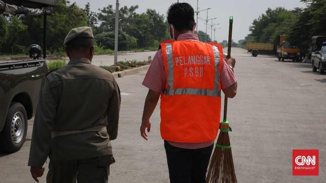 Pengendara motor maupun mobil yang terjaring saat razia masa PSBB Transisi di kawasan Kanal Banjir Timur Marunda, Jakarta Utara, Kamis, 18 Juni 2020. Pelanggar ini tidak mengenakan masker saat keluar rumah dengan sanksi melakukan kerja sosial. CNNIndonesia/Safir Makki