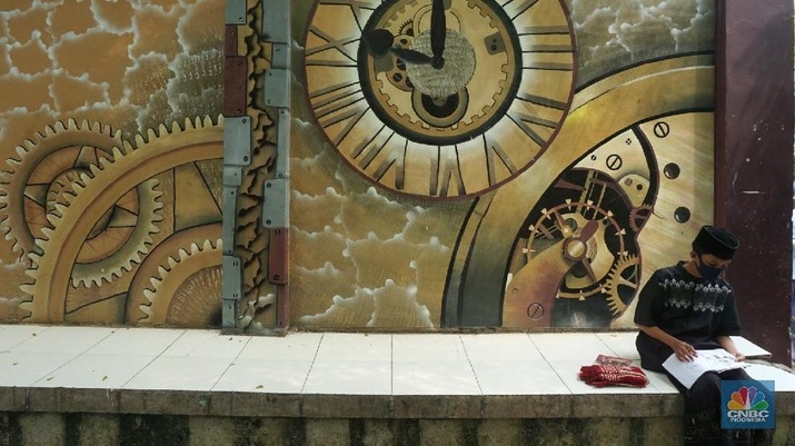 Suasana Pesantren An-Nuqthah, Tangerang Banten, sejumlah santri kembali berdatangan usai belajar di rumah selama pandemi corona. 18/6/20. CNBC Indonesia/Tri Susilo Para santri juga harus mengenakan masker walaupun sudah berada di dalam pesantren. Pemulangan santri ke pesantren dilakukan selama beberapa tahap dalam satu minggu. Ini dilakukan guna menghindari penumpukan orang dalam satu waktu. Pada tahap awal, santri yang kembali baru sekira 15 persen dari total 1.500 santri. Sementara, sebagian orangtua masih khawatir akan penularan virus corona di dalam pesantren. Karena itu mereka membekali buah hatinya dengan cairan pembersih tangan, vitamin dan persediaan masker. Sementara pengelola pesantren menyebut, kebijakan membuka kembali aktifitas belajar tatap muka karena pihaknya merasa sudah sanggup menerapkan protokol kesehatan di dalam pesantren. Guna penerapan protokol kesehatan, pihak pengelola melakukan sterilisasi lingkungan pesantren secara rutin, menata ulang kamar-kamar tidur para santri, dan menjaga jarak antar individu, baik dalam setiap kegiatan belajar mengajar maupun ibadah. Pantauan CNBC Indonesia Dilapangan para santri yang melakukan ibadah harus tetap jaga jarak didalam masjid. Santri yang balik ke pesantren belum semuanya berdatangan, kemungkinan gelombang kedua akan datang pada bulan Juli 2020 mendatang. (CNBC Indonesia/ Tri Susilo)