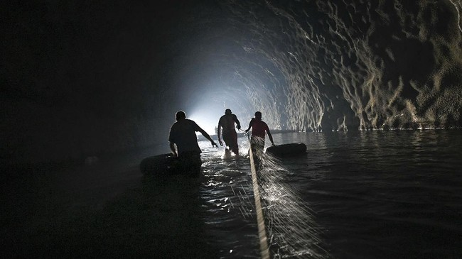 Locals wade through water inside an abandoned highway tunnel as they follow a safety line and drag inner tubes as they work to repair a self-created water system in Caracas, Venezuela, Thursday, June 11, 2020. Without potable water from the respective government authorities, residents of the Esperanza neighborhood have organized to create their own water supply collected from inside the never completed Baralt highway tunnels. (AP Photo/Matias Delacroix)