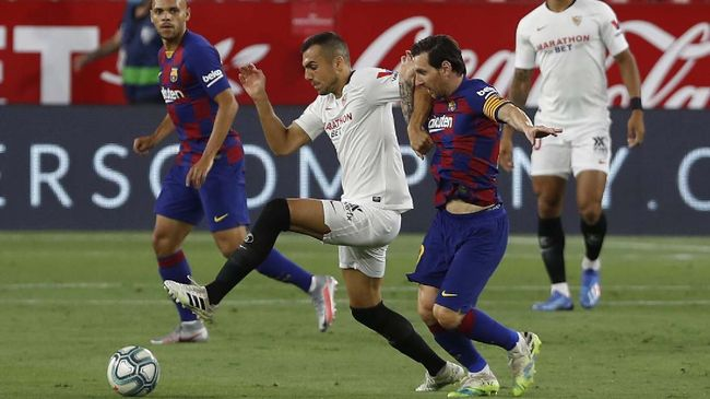 FC Barcelona's Lionel Messi, right, vies for the ball with Sevilla's Joris Gnagnon during the Spanish La Liga soccer match between Sevilla and FC Barcelona at the Ramon Sanchez-Pizjuan stadium in Seville, Spain, Friday, June 19, 2020. (AP Photo/Angel Fernandez)