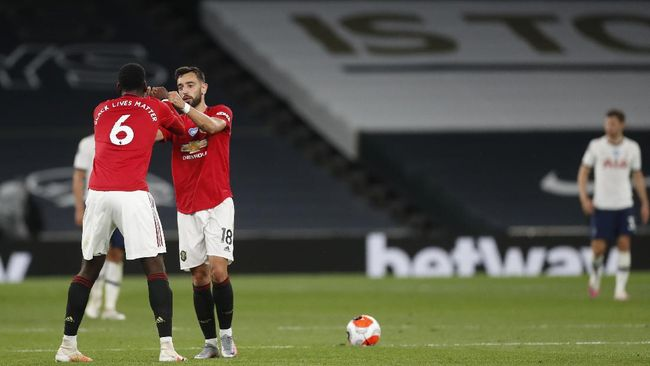 Manchester United's Bruno Fernandes, right, celebrates with Paul Pogba after scoring his side's first goal during the English Premier League soccer match between Tottenham Hotspur and Manchester United at Tottenham Hotspur Stadium in London, England, Friday, June 19, 2020. (AP Photo/Matt Childs, Pool)