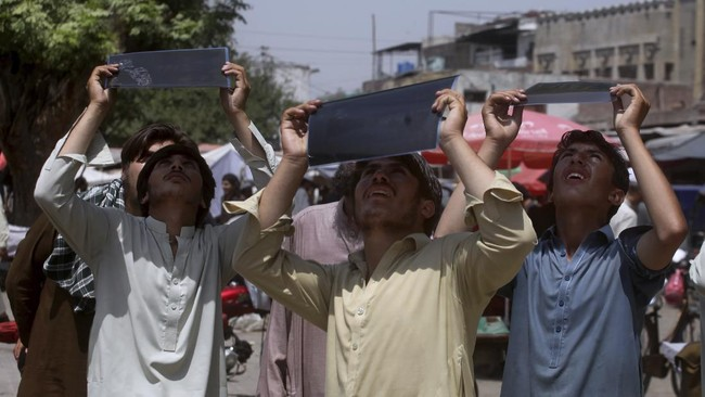 People observe the partial solar eclipse through x-ray sheets at a market in Peshawar, Pakistan, Sunday, June 21, 2020. (AP Photo/Muhammad Sajjad)