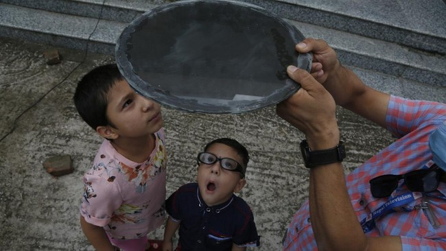 Nepalese children watch solar eclipse through a dark glass in Kathmandu, Nepal, Sunday, June 21, 2020. (AP Photo/Niranjan Shrestha)