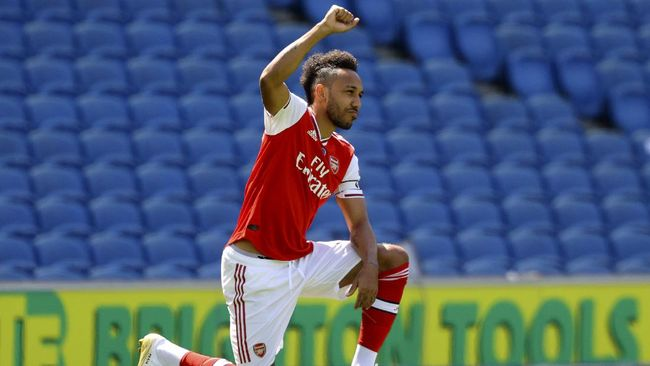 Arsenal's Pierre-Emerick Aubameyang takes the knee before the start of the English Premier League soccer match between Brighton & Hove Albion and Arsenal at the AMEX Stadium in Brighton, England, Saturday, June 20, 2020. (Richard Heathcote/Pool via AP)