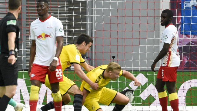 Dortmund's Erling Braut Haaland, center on the ground, celebrates with his teammates after he scored his side's first goal during the German Bundesliga soccer match between RB Leipzig and Borussia Dortmund in Leipzig, Germany, Saturday, June 20, 2020. (AP Photo/Jens Meyer, Pool)