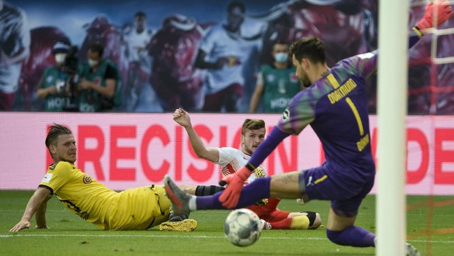 Dortmund's goalkeeper Roman Buerki, right, saves as Leipzig's Timo Werner, center, tries to score past Dortmund's Lukasz Piszczek during the German Bundesliga soccer match between RB Leipzig and Borussia Dortmund in Leipzig, Germany, Saturday, June 20, 2020. (AP Photo/Jens Meyer, Pool)