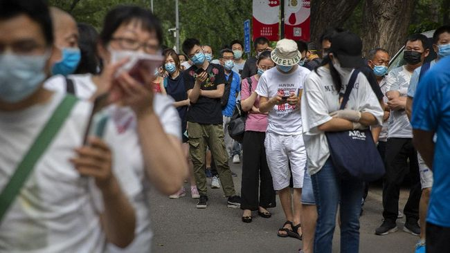People wait in line at a COVID-19 testing site after they were ordered by the government to be tested after potentially being exposed to the coronavirus outbreak at a wholesale food market in Beijing, Wednesday, June 17, 2020. As the number of cases of COVID-19 in Beijing climbed in recent days following an outbreak linked to a wholesale food market, officials announced they had identified hundreds of thousands of people who needed to be tested for the coronavirus. (AP Photo/Mark Schiefelbein)