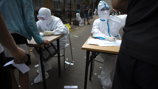 Workers in protective suits register people at a COVID-19 testing site for those who were potentially exposed to the coronavirus outbreak at a wholesale food market in Beijing, Wednesday, June 17, 2020. As the number of cases of COVID-19 in Beijing climbed in recent days following an outbreak linked to a wholesale food market, officials announced they had identified hundreds of thousands of people who needed to be tested for the coronavirus. (AP Photo/Mark Schiefelbein)