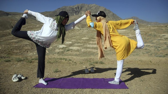 Afghan enthusiasts women perform yoga to mark International Yoga Day during the COVID-19 pandemic lockdown, on the outskirts of Kabul, Afghanistan, Sunday, June 21, 2020. (AP Photo/Rahmat Gul)