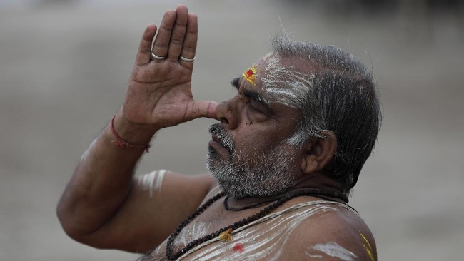 A Hindu holy man performs yoga at Sangam, the confluence of rivers the Ganges and the Yamuna in Prayagraj, India, Sunday, June 21, 2020. Sunday marked International Yoga Day. (AP Photo/Rajesh Kumar Singh)