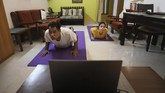A couple practices Yoga in their home to mark International Yoga day through an online class in New Delhi, India, Sunday, June 21, 2020. (AP Photo/Manish Swarup)