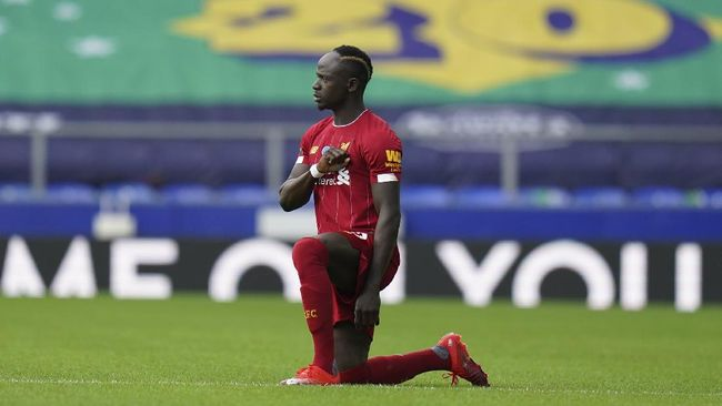 Liverpool's Sadio Mane takes the knee before the English Premier League soccer match between Everton and Liverpool at Goodison Park in Liverpool, England, Sunday, June 21, 2020. (AP photo/Jon Super, Pool)