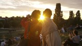 Two women take photos as the sun sets on Summer Solstice, the longest day of the year at the public park Mauerpark in Berlin, Germany, Sunday, June 21, 2020. (AP Photo/Markus Schreiber)