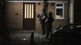 """Armed police officers stand by a door at a block of flats off the Basingstoke Road in Reading after an incident at Forbury Gardens park in the town centre of Reading, England, Saturday, June 20, 2020. Several people were injured in a stabbing attack in the park on Saturday, and British media said police were treating it as """"terrorism-related."""" (Steve Parsons/PA via AP)"""