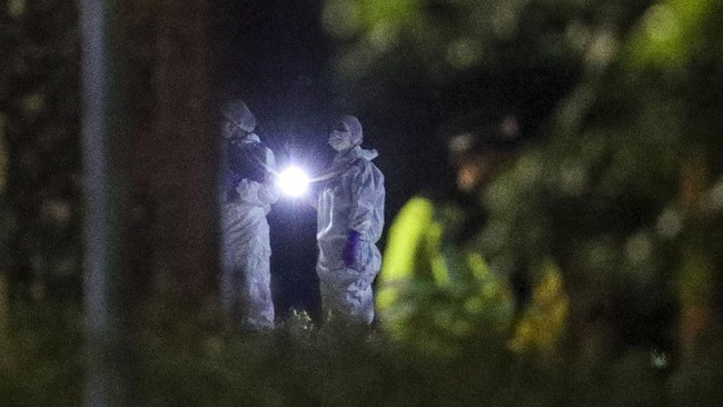 Forensic officers work at Forbury Gardens park where a summer-evening stabbing attack took place Saturday, in Reading, England, early Sunday June 21, 2020. (Steve Parsons/PA via AP)