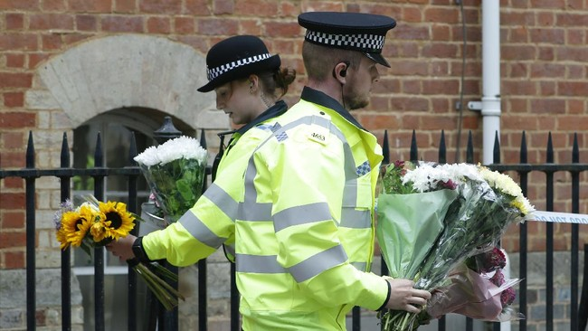 Police officers collect flowers left at the Abbey gateway of Forbury Gardens following a multiple stabbing attack which took place on Saturday, in Reading, England, Sunday June 21, 2020. Police say a stabbing rampage in Britain that killed three people as they sat in a park on a summer evening is being considered a terrorist attack. A 25-year-old man believed to be the lone attacker is in custody. (AP Photo/Alastair Grant)